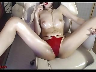 Korean beauty in red swimsuit oils her body
